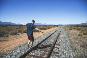 Mann geht über Gleise